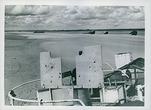 Vintage photo of The re-birth of France: Landing craft and beach equipment lie along the rippled sands of Utah beach, once a scene of battle.