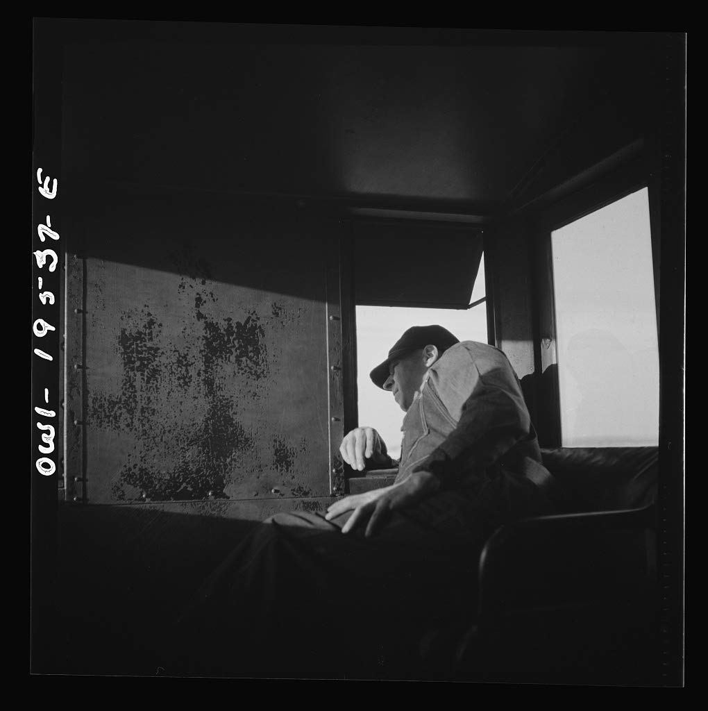 Reproduced Photo of Rear brakeman M. H. Burdette, watching the train from his window in the cupola on the Atchison, Topeka and Santa Fe Railroad, between Chillicothe, Illinois a 1943 Delano C Jack 74a