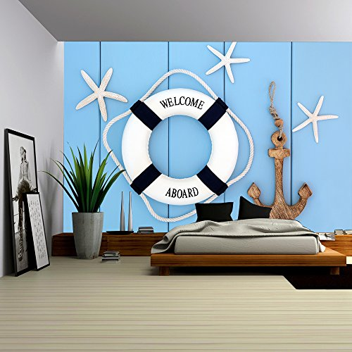 Decorative lifebuoy anchor and starfish sea shells over wooden blue background
