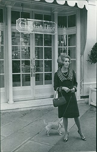 Vintage photo of Yvette de Tothschild posing with her dog in front of a Christian Dior Boutique.
