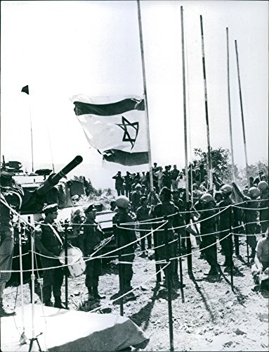 """Vintage photo of The last ceremonial lowering of the Israeli flag before the withdrawal from Kuneitra, captured during the """"Yom Kippur"""" war: shortly after this ceremony, the Syrians resumed control, 1974."""