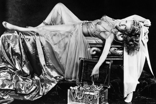 (Rita Hayworth in Salome iconic sexy image revealing costume lying on bed 24x36 Poster)