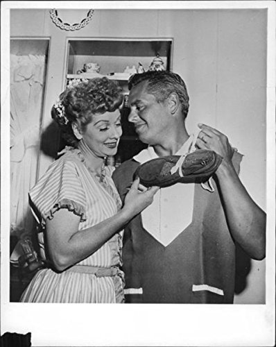Reprint of Lucille Ball and Desi Arnaz holding shoes