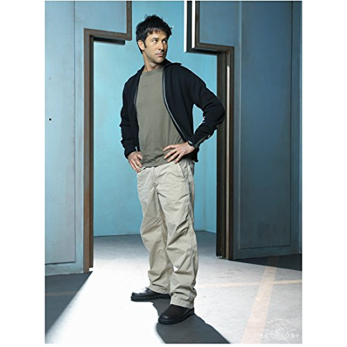 Joe Flanigan 8x10 Inch Photo Stargate Atlantis 6 Bullets The Other Sister Light Khaki Pants Black Sweater Over Grey Tee Funky Doorway in Background Pose 3 kn