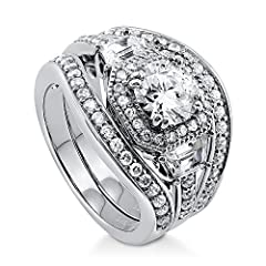 This 3 piece art deco halo ring set will take your breath away with its impeccable brilliance and vintage style allure. Made of rhodium plated fine 925 sterling silver. Features 1.28 carat round cut clear cubic zirconia (7mm) in 4-pron...