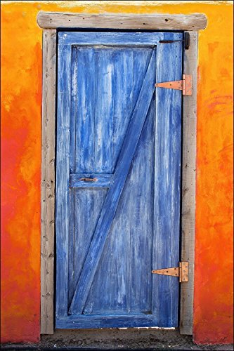 Photograph of very colorful American Southwest blue wood barn door on an orange adobe wall.
