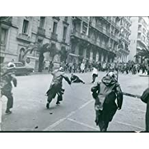 Vintage photo of A protest on the street with police men running after the civilians during the war in Algeria