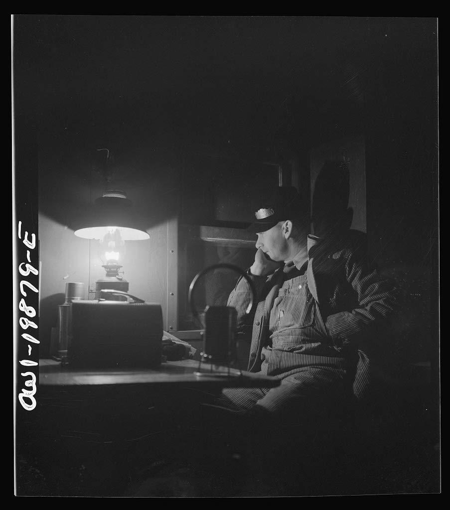 Reproduced Photo of Waynoka, Oklahoma. Brakeman Jack Torbet, sitting at the window of the caboose pulling out of Waynoka, Oklahoma on the Atchison, Topeka, and Santa Fe Railroad 1943 Delano C Jack 28a