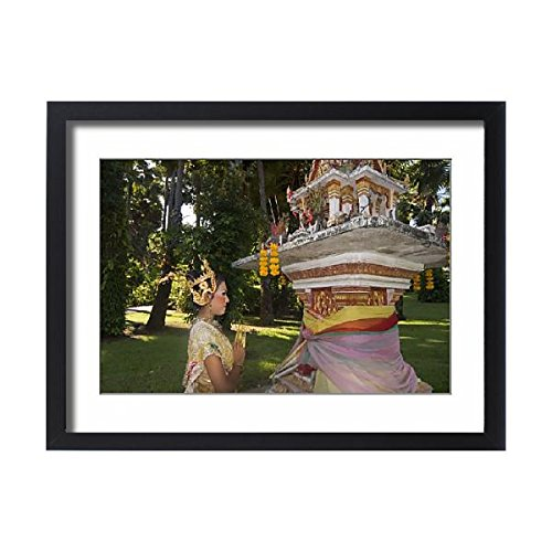 Framed 24x18 Print of Girl in traditional Thai clothes praying at a spirit house (1207557) by Robert Harding