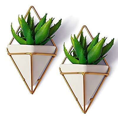 "California Home Goods Modern Hanging Planter Pots (2-Pack), Small Decorative Wall Planters for Cactus Decor & Hanging Plants, Wall Hanging Ceramic Planter with Brass Wire Frame, White Plant Decor - MODERN HANGING DECOR PERFECT FOR INDOOR HOUSEPLANTS: Measuring 4.5"" x 2.75"" x 7.25"" per hanging pot, the geometric plant pots or white small hanging pots can house a variety of mini succulents like cactus, moss, foliage, echeveria, haworthia, aloe, and more. Not having a green thumb is no excuse-- this geometric wall decor is also perfect to place faux air plants or artificial succulents. There's nothing that screams good taste like your own personal hanging wall terrarium. EASY TO INSTALL WALL HANGING PLANTERS: Our decorative planter set is complete with the screws you need to easily install the geometric vases onto your lonely walls. Because the brass wire frame holds and keeps the geometric pot against your wall, it's so easy to clean and re-arrange as often as you want to. And should you want to change the hanging plants, simply pull the mini vase from the brass frame - no need to unscrew and re-screw. GEOMETRIC HANGING VASES THAT'LL LIVE UP TO YOUR EXPECTATIONS: Here at California Home Goods, we are so confident in the quality of our products that we provide a money-back to ensure your satisfaction; and that includes our Modern Wall Hanging Planters. If in case you're unhappy with your purchase of our geometric wall vases, simply reach out to us within 30 days so we could improve your overall experience. - living-room-decor, living-room, home-decor - 51CsCUYAwuL. SS400  -"