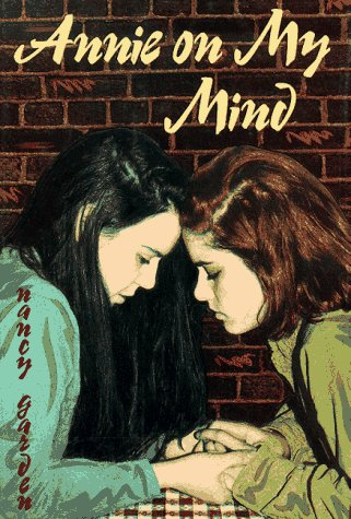 Two girls hold hands across a small table and press their foreheads together with their eyes closed
