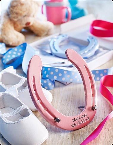 Good Luck Hufeisen mit Gravur des Vornamen und Geburtsdatum des Babys Zur Geburt oder Taufe in rosa auf hellrosa Kissen.