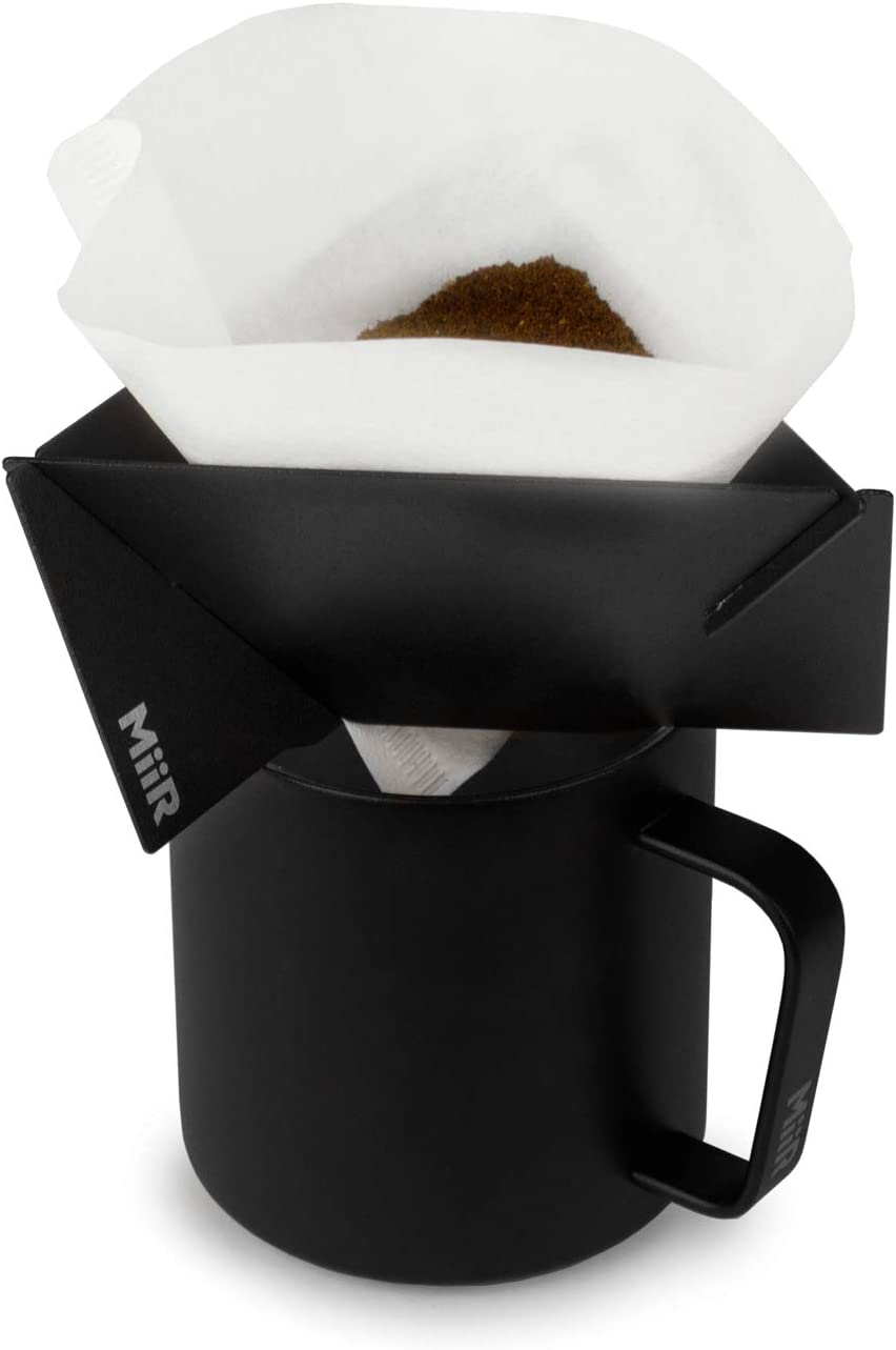 This is an image of a black coffee dripper with coffee beans above it and a straining paper, on top of a black mug.