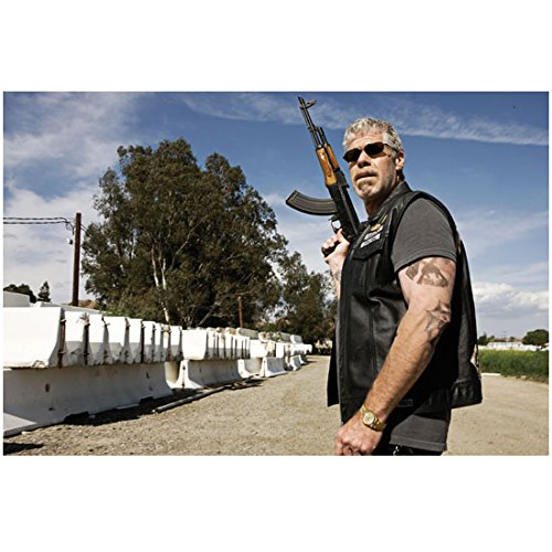 Sons of Anarchy Ron Perlman Wearing Sunglasses Standing Outside By Cement Blocks Holding Gun Up 8 X 10 Inch - Stonewalls Block