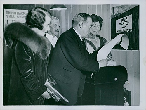Vintage photo of Stanley Baldwin reading a letter, other people looking at him.