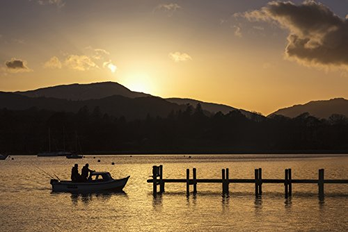 Silhouette of fishermen in a boat arriving at a dock on a lake at sunset; Keswick, Cumbria, England Poster Print (19 x 12) ()