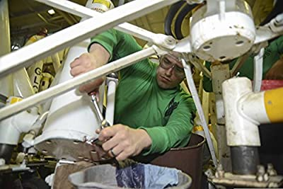 U.S. Navy Aviation Support Equipment Technician 3rd Class Taylor Garza repairs a hydraulic jack in t