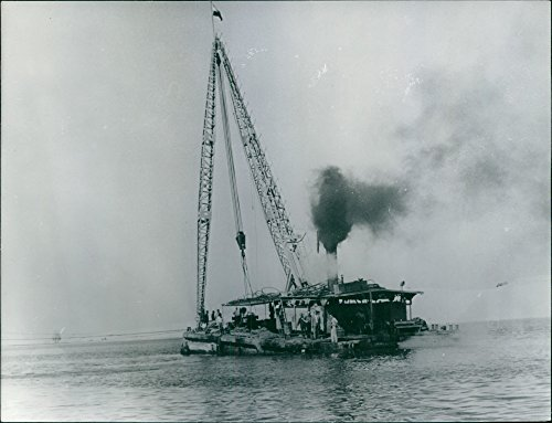 Vintage photo of Clearing the Suez canal with international hep and backing, the Suez Canal Board has begun the task of clearing the Suez canal of war debris. Here, the Egyptian floating crane