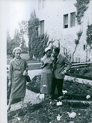 Vintage photo of Prince Sadruddin Aga Khan with his wife Nina Dyer, smelling the flower, while his mother Andr233;e stands aside.