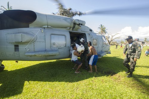 Philippine citizens take supplies from an SH-60B Sea Hawk helicopter from the Scorpions of Helicopte