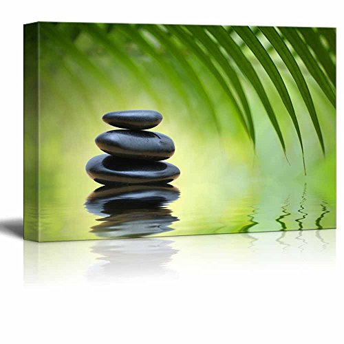 Green Bamboo Leaves over Zen Stones Pyramid Reflecting in Water Surface for Spa Decor