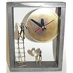 Desk clock in a black wooden frame with two bronze figures.