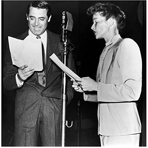 Cary Grant 8 inch x 10 inch PHOTOGRAPH Grant in Dark Pinstriped Suit with Lady in Light Coloured Suit Talking into Microphone Mid Black and White
