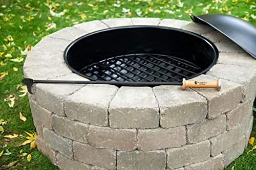 Fire pit poker stick resting on a round fire pit.