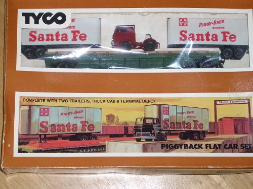 (Vintage 1968 (5-68) TYCO Piggyback Flat Car Set #T-348 - HO Scale in original box. Complete with two Santa Fe trailers, truck cab & terminal depot. Includes Instructions. Back of box shows photos of Accessories 347, 348, 349, 862, 906, 908, 925, 926, 928, 930 & 931 and Exclusive Tyco-Matic Electric Switches.)