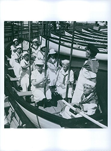 Vintage photo of Old ladies wearing sailor uniforms on a rowing boat.
