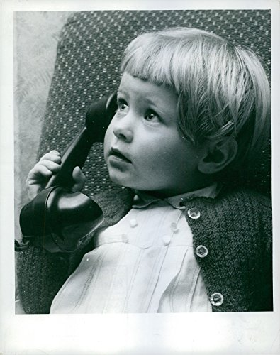 Learn Telephone (Vintage photo of A young girl learns how to use a telephone.)