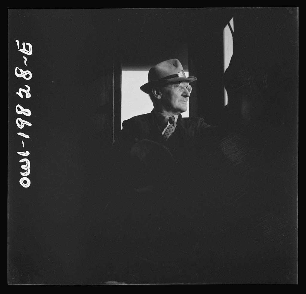 Reproduced Photo of Conductor W. E. Zink, watching the train from his window in the cupola of the caboose on the Atchison, Topeka, and Santa Fe Railroad between Emporia and Well 1943 Delano C Jack 02a