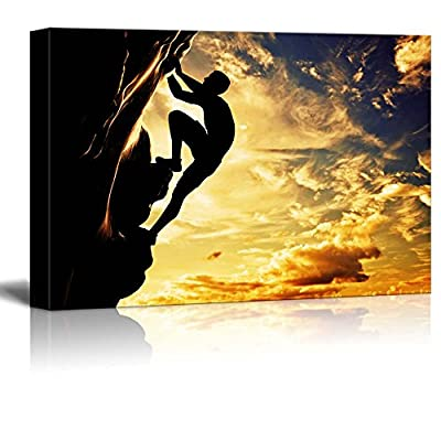 A Silhouette of a Man Climbing on Rock Mountain Cliff at Sunset Concept of Bravery Determination - Canvas Art Wall Art - 24