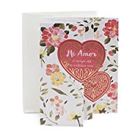 """Send your love a beautiful birthday greeting this year with this card featuring watercolor flowers and leaves with two hearts filled with gold scrollwork. The message on the front of the card reads, """"Mi Amor El tiempo sólo te embellece más."""" ..."""