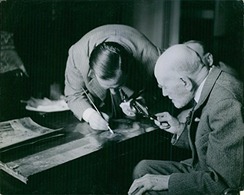 Vintage photo of American art historian Bernard Berenson inspecting a painting by a magnifying glass, while a man painting with brush ()