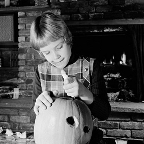 Girl preparing pumpkin for Halloween Poster Print (24 x 36)]()