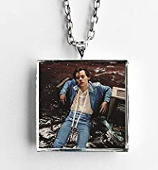 "This is a necklace featuring album art of the Self Titled import version record by Harry Styles sealed in a silvertone metal setting. The album cover pendant is 1"" and on a 20"" long silvertone neck chain. The necklace is individually handcraf..."