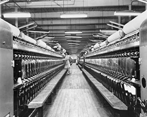 Side profile of a woman working on a spinning frame in a textile ...