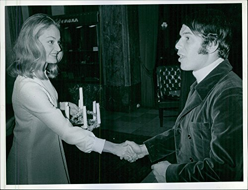 Vintage photo of Kerstin Asp, holding Lucia crown, shaking hand with man.