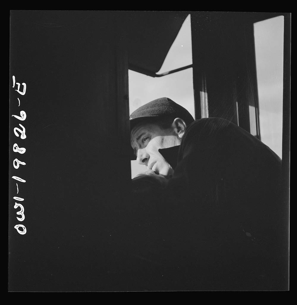 Reproduced Photo of Brakeman H. L. Duffield, watching the train from the window in the cupola of the caboose on the Atchison, Topeka, and Santa Fe Railroad between Emporia and W 1943 Delano C Jack 01a