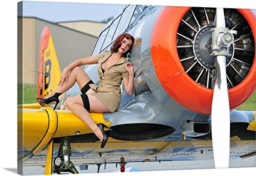Christian Kieffer Premium Thick-Wrap Canvas Wall Art Print entitled 1940's style pin-up girl posing on a T-6 Texan training aircraft by Canvas on Demand