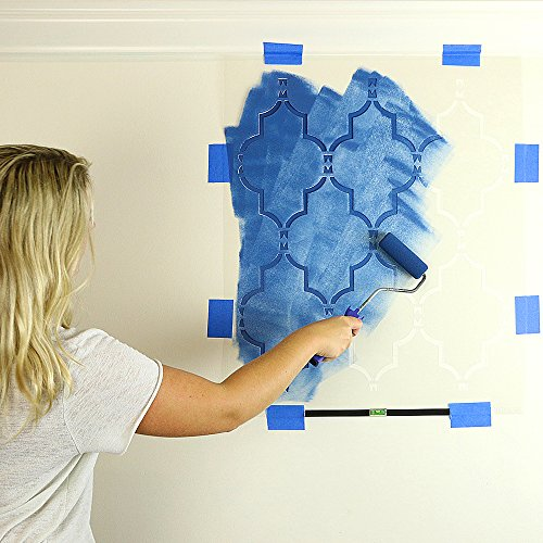 Woman applying stencil paint on an interior wall.