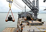 A 154,000-pound Manitowoc crane is lifted off the deck of the Military Sealift Command crane ship SS