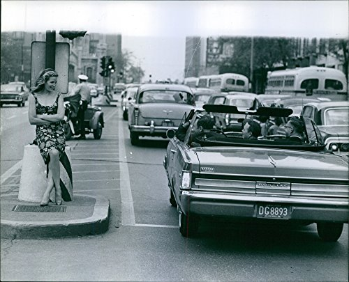 Vintage photo of Alexandra Stewart is sitting on a lamp post in the middle of the street.1963
