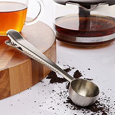 Stainless steel coffee scoop with ground coffee bag clip seal a silver spoon.