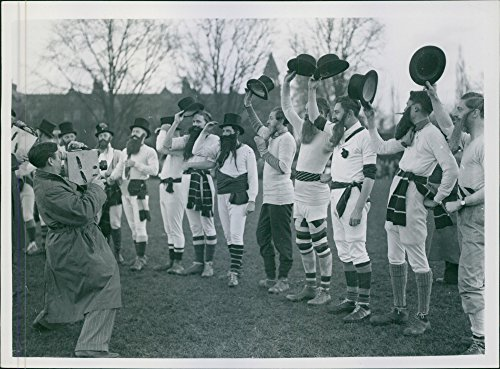 Vintage photo of British players standing and holding hats, while photographer taking -