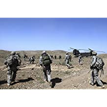 April 5, 2010 - U.S. Army Soldiers run back to their CH-47 Chinook helicopters after searching safe houses and clearing a suspected Cache Site in Bak, Khowst province, Afghanistan Poster Print (17 x 11)
