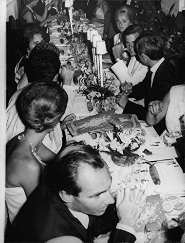 Vintage photo of Aga Khan IV in discussion during meal.