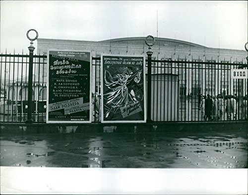 Vintage photo of Two large posters posted on the gates of a building. -