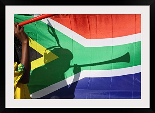 GreatBIGCanvas ''Shadow of soccer supporter blowing vuvuzela, South African flag in background'' Photographic Print with Black Frame, 36'' x 24'' by greatBIGcanvas